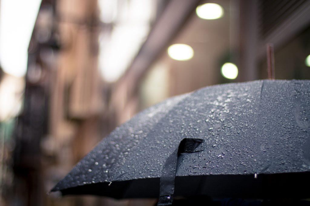 大雨で傘をさす